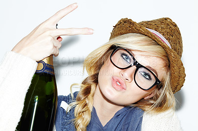 Buy stock photo A gorgeous young woman gesturing while holding a bottle of champagne