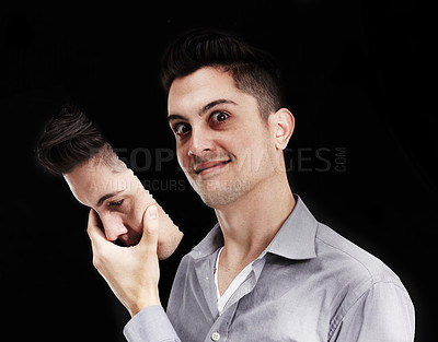 Buy stock photo Young man lifting a mask off his face and revealing a deranged expression