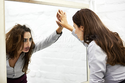 Buy stock photo Attractive young woman looking in a mirror and seeing a hideous reflection
