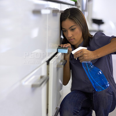 Buy stock photo Young woman cleaning the handles of the drawers in a kitchen
