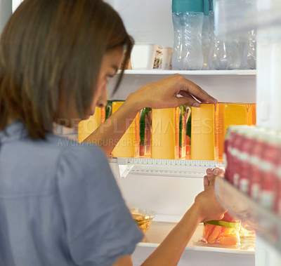 Buy stock photo Young woman organising the contents of her fridge carefully