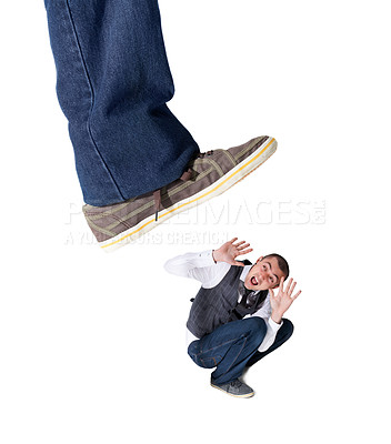 Buy stock photo A fearful young man lying on the ground with a giant foot ready to squash him