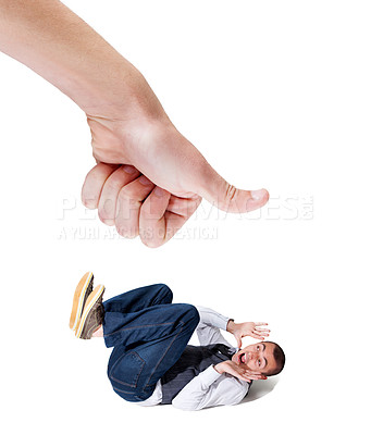 Buy stock photo A fearful young man lying on the ground with a giant thumb looking to squash him