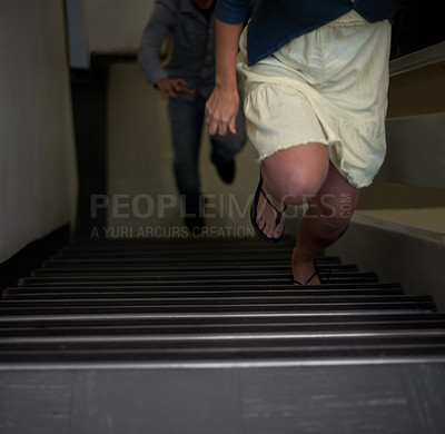 Buy stock photo Cropped view of a woman trying to run away from an attacker on the stairs