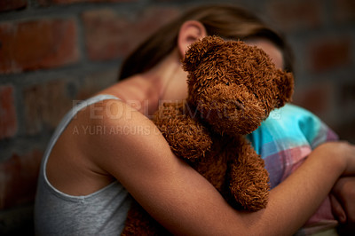 Buy stock photo Abused little girl holding a teddy bear tightly while huddled over