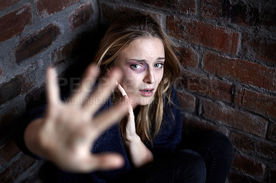 Buy stock photo Abused young woman huddled and crouching in a corner while reaching out in a stop gesture