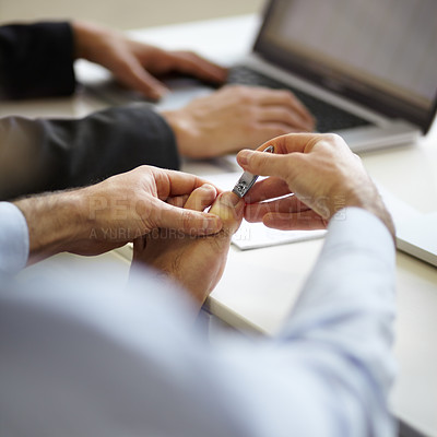 Buy stock photo A young man clipping his toenails on his desk at work