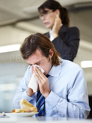 Buy stock photo Young businessman blowing his nose over a sandwich while a coworker stands behind him