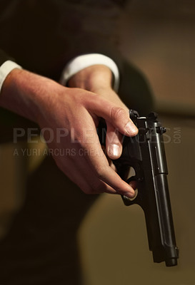 Buy stock photo Cropped view of a man's hands holding a gun