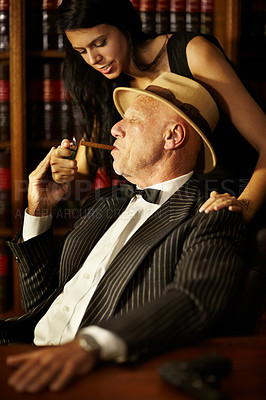 Buy stock photo Aged mob boss wearing a hat and looking serious while a woman lights up a cigarette for him