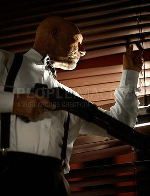 Buy stock photo Mob boss looking out through the blinds while holding a shotgun