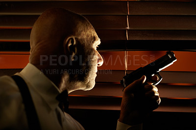 Buy stock photo Mob boss looking out through the blinds while holding a handgun