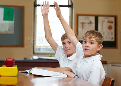 Buy stock photo Two young schoolboys raising their hands in a classroom