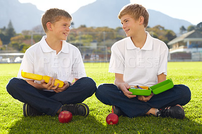 Buy stock photo Two young schoolboys sitting on the grass about to eat their lunch