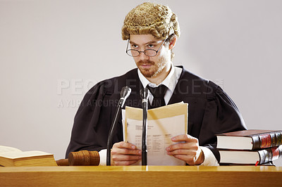 Buy stock photo Serious young judge sitting in the courtroom with a stern facial expression