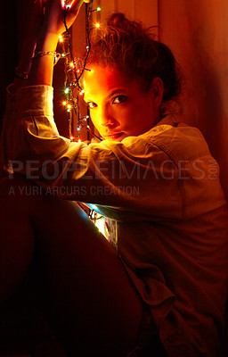 Buy stock photo A moody portrait of a young woman lit by christmas lights