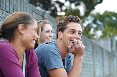 Buy stock photo A shot of a guy and two girls sharing a laugh together while sitting outside