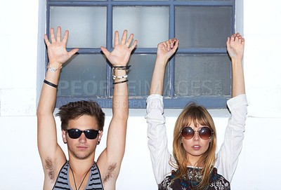 Buy stock photo Portrait of two young hipsters staring at the camera with their arms raised in the air