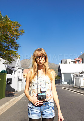Buy stock photo A stylish young girl with a vintage camera standing in the middle of a road in a quaint residential neighbourhood