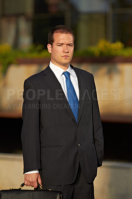 Buy stock photo Portrait of a serious businessman holding a briefcase
