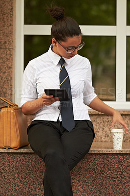 Buy stock photo A beautiful young woman sitting with her digital tablet and reaching for her coffee