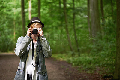 Buy stock photo Closeup portrait of a young man taking pictures with a vintage camera in the forest with copyspace