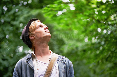 Buy stock photo A young man takes in his surroundings while hiking in a forest
