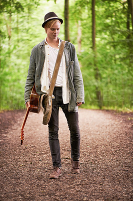 Buy stock photo A full length shot of a stylish young man carrying a guitar while waking in the forest