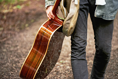 Buy stock photo A cropped closeup shot of a young man carrying a guitar while walking down a forest path