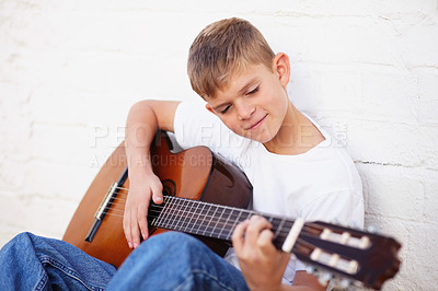 Buy stock photo Musical young boy strumming his guitar while sitting against a wall