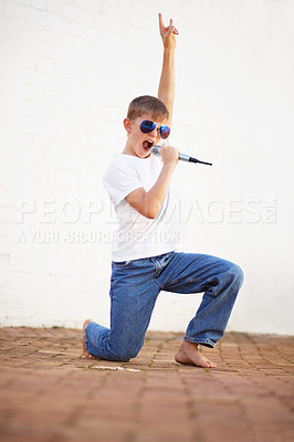 Buy stock photo Young boy lost in song while holding a microphone and wearing sunglasses