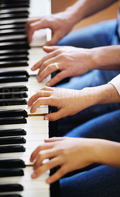 Buy stock photo Young boy playing the piano diligently alongside his tutor - cropped