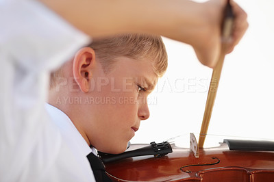 Buy stock photo Musical young boy completely focused on playing his violin