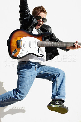 Buy stock photo Little boy playing the electric guitar and jumping with a rockstar attitude