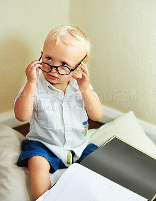 Buy stock photo Cute baby boy with spectacles sitting with a book on the floor