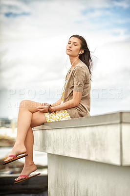 Buy stock photo Pretty young woman listening to music while sitting on a rooftop