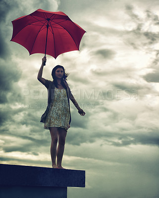 Buy stock photo Cute young woman holding an umbrella while standing on a rooftop