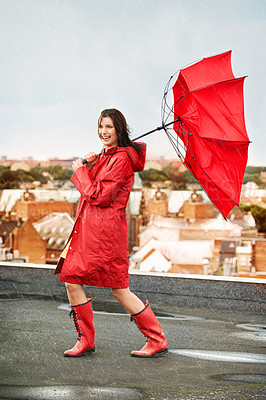 Buy stock photo Young woman laughing while being battered by rain and wind on a rooftop