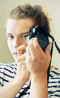 Buy stock photo Portrait of a young man with curly hair holding up a camera to his face