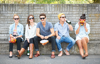 Buy stock photo Young hipster friends drinking together while sitting outdoors