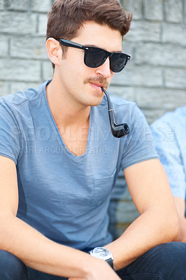 Buy stock photo Handsome young hipster smoking a pipe while sitting outdoors