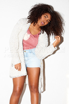 Buy stock photo Young African hipster leaning to one side and twirling her hair