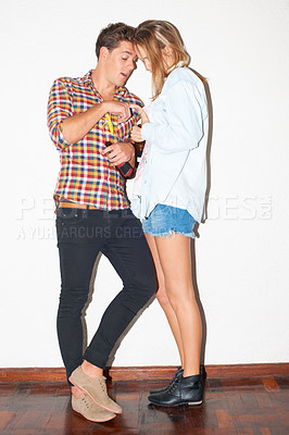 Buy stock photo Young hipster couple fooling around while drinking and standing against a white wall