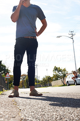 Buy stock photo Cropped view of a young hipster guy standing in the street with his girlfriend sitting in the distance behind him