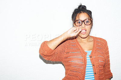 Buy stock photo Young hipster woman biting her finger while standing against a white wall