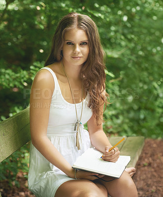 Buy stock photo Portrait of a pretty young woman sitting in the forest and writing in her journal