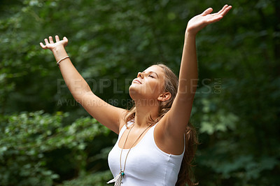 Buy stock photo A pretty young woman with her arms raised while standing in a forest