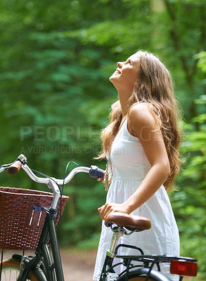 Buy stock photo A beautiful young woman walking in the forest with her bicycle