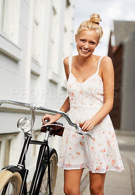 Buy stock photo A beautiful young blonde woman standing with her vintage bicycle