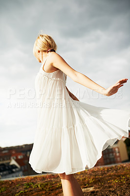 Buy stock photo Low angle shot of a gorgeous young woman twirling on a rooftop with clouds in the background